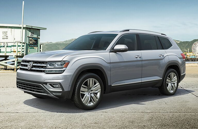 silver Volkswagen Atlas parked by beach, carnival area