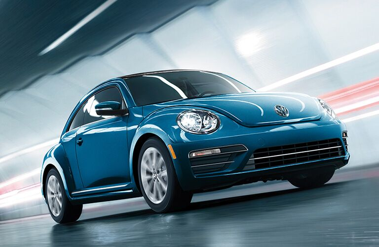 blue Volkswagen Beetle driving through tunnel