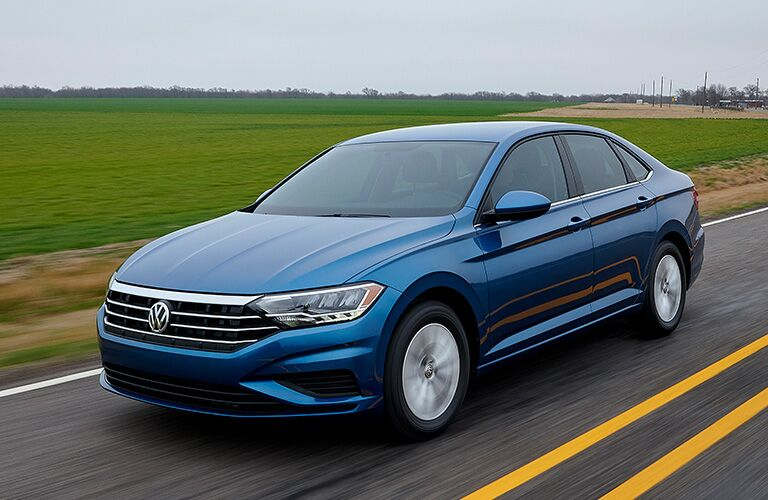 blue Volkswagen Jetta driving by farmland