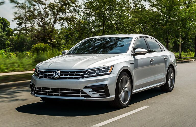 silver Volkswagen Passat driving by trees