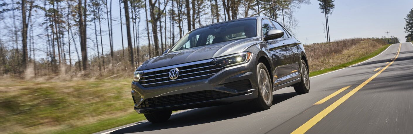 Gray 2019 Volkswagen Jetta driving down a tree-lined road