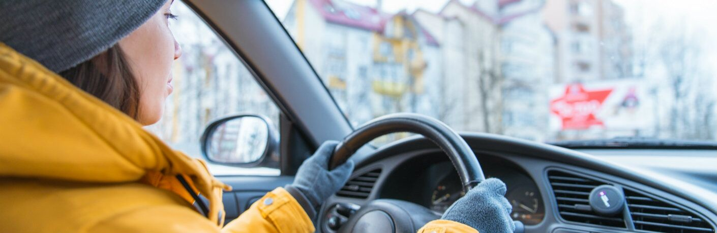 Woman bundled up while driving in the winter