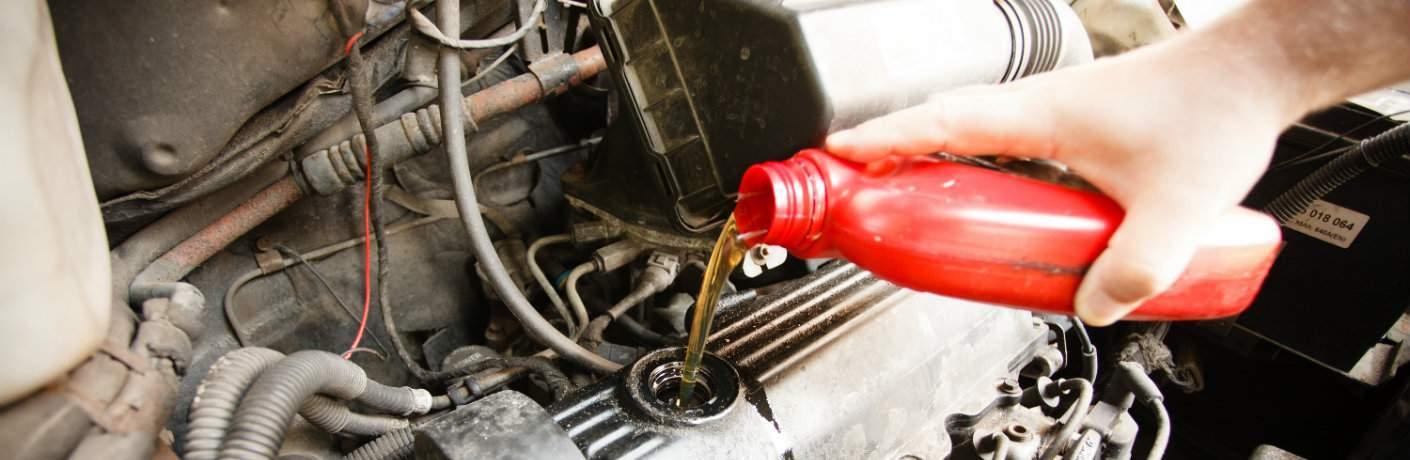 Mechanic adding fluid to a vehicle