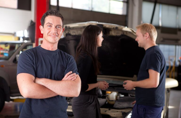 Mechanic with folded arms with different mechanic talking to a female driver