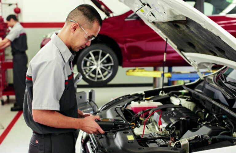 Mechanic performing electrical tests on a vehicle