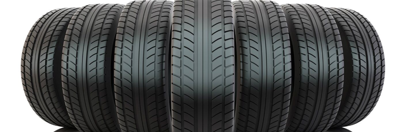 a line of clean, fresh, new automotive tires and their treads