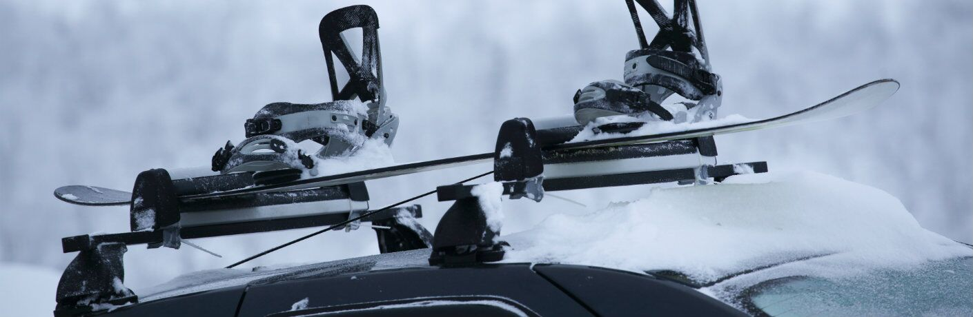 the top of a car with a snowboard and boots clipped into the roof rack rails