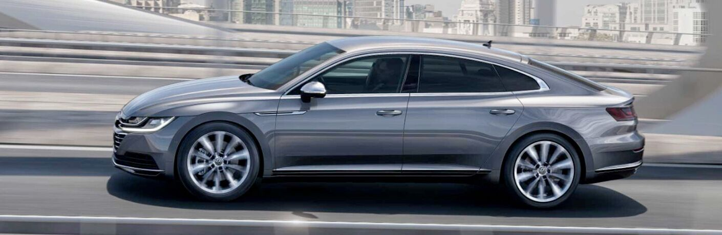Side view of a silver 2019 Volkswagen Arteon driving up a city highway.