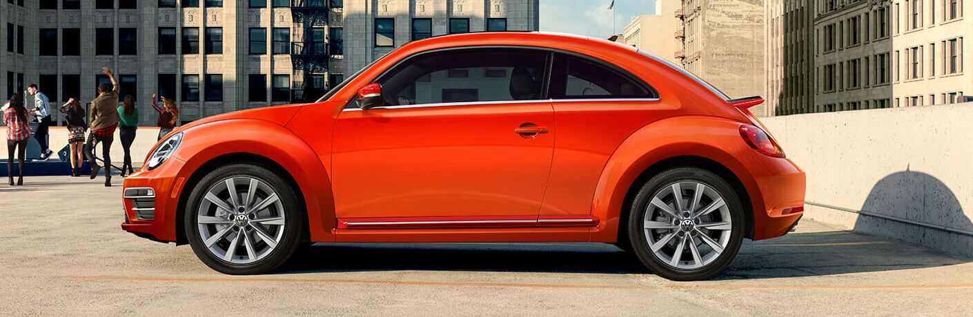 Side view of an orange 2019 Volkswagen Beetle on a parking ramp as a bunch of youngsters jump around nearby.