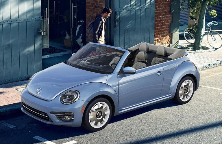 Blue 2019 Volkswagen Beetle Convertible that a man is walking up to on a city street.