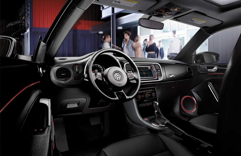 Interior front cabin of the 2019 Volkswagen Beetle, with some people socializing out beyond the windshield.