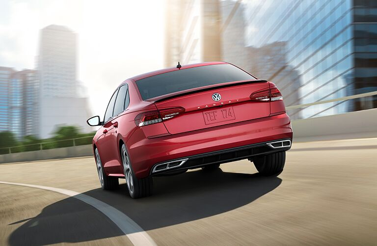 Red 2020 Volkswagen Passat cruises away around a city highway curve.