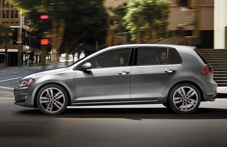 Silver Volkswagen Golf ambles through a city loaded comfortable with four occupants.