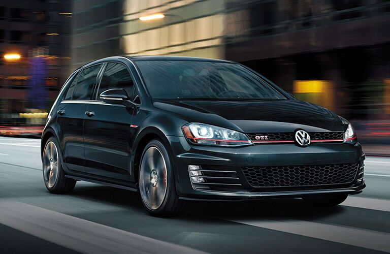 Black Volkswagen Golf GTI zooms up a city street.