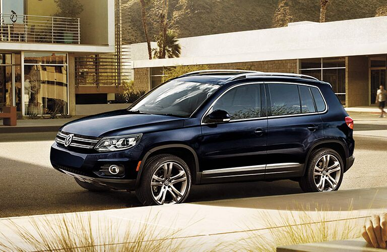 Deep blue Volkswagen Tiguan parked in a modern neighborhood.