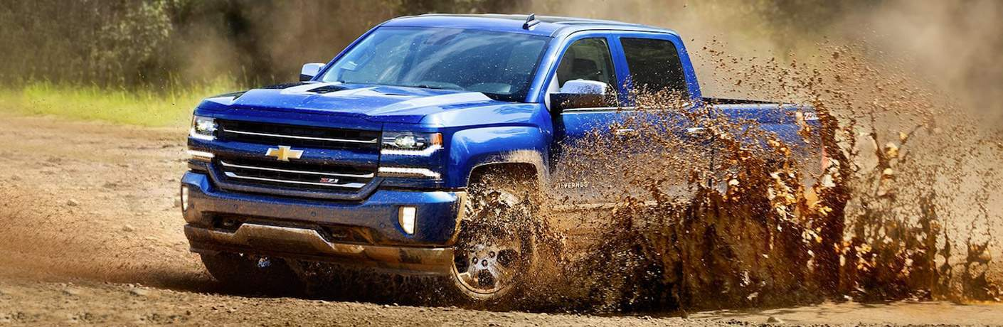 2018 Chevy Silverado 1500 blue side view in the mud