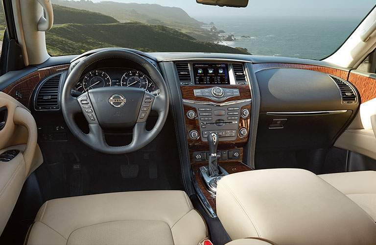 interior of 2018 nissan armda including steering wheel, dashboard, and infotainment system looking out over sea cliff
