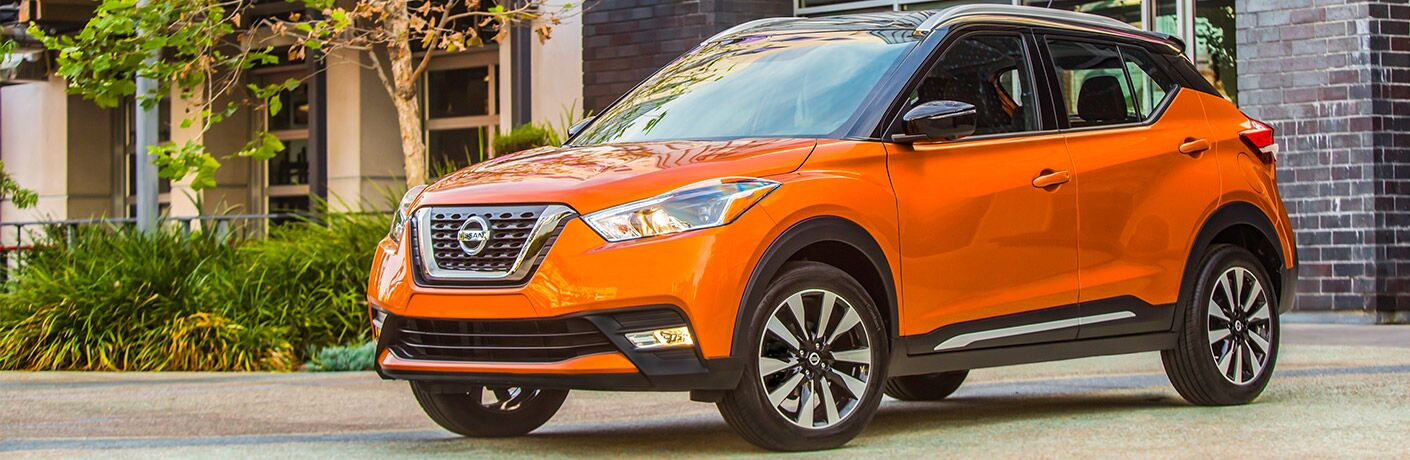 2018 Nissan Kicks exterior front fascia and drivers side on pavement in front of building with tree