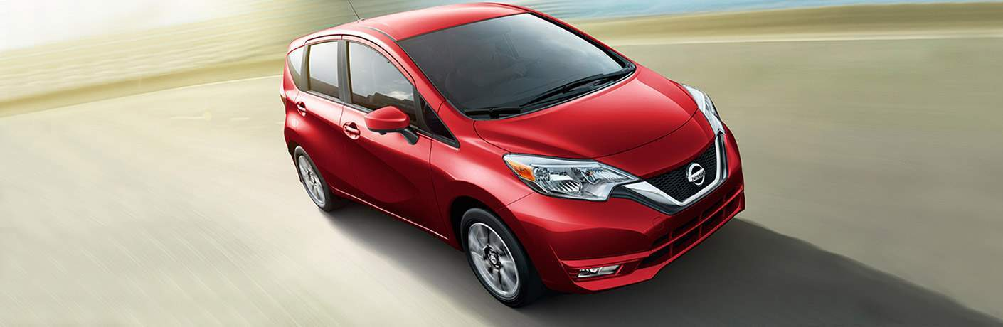 red 2018 nissan versa note driving on empty road