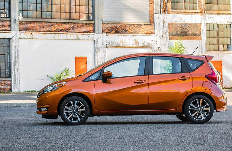 side view of orange 2018 nissan versa note with empty warehouse behind