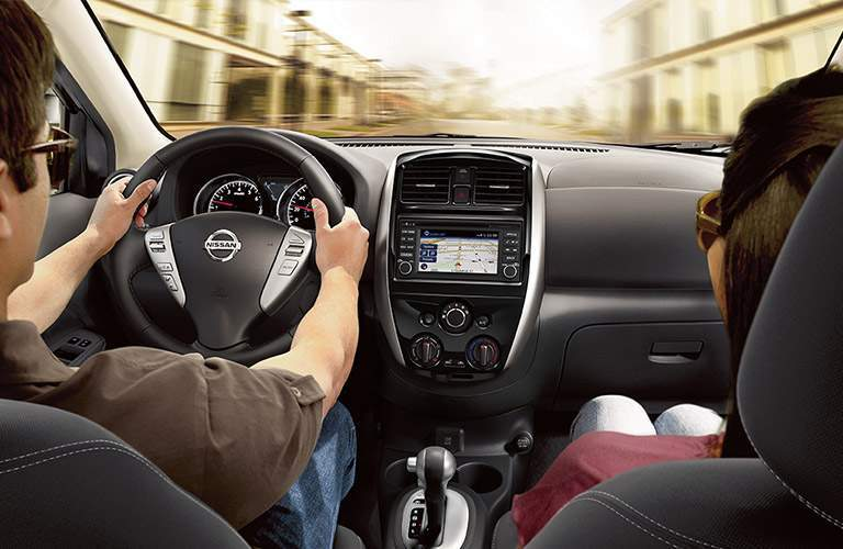 man and woman in front seats of 2018 nissan versa driving