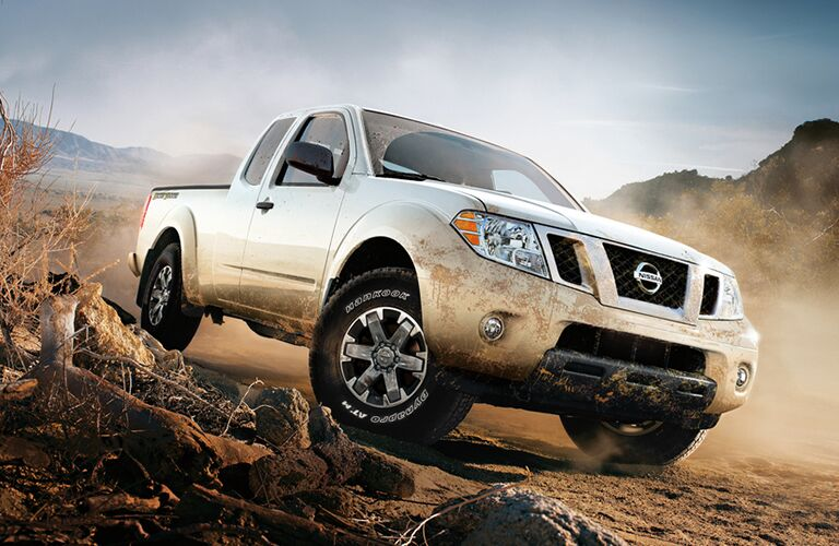white Nissan Frontier driving on sandy dirt road