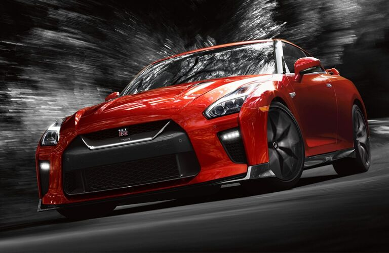 red Nissan GT-R turning a corner on a back road highway