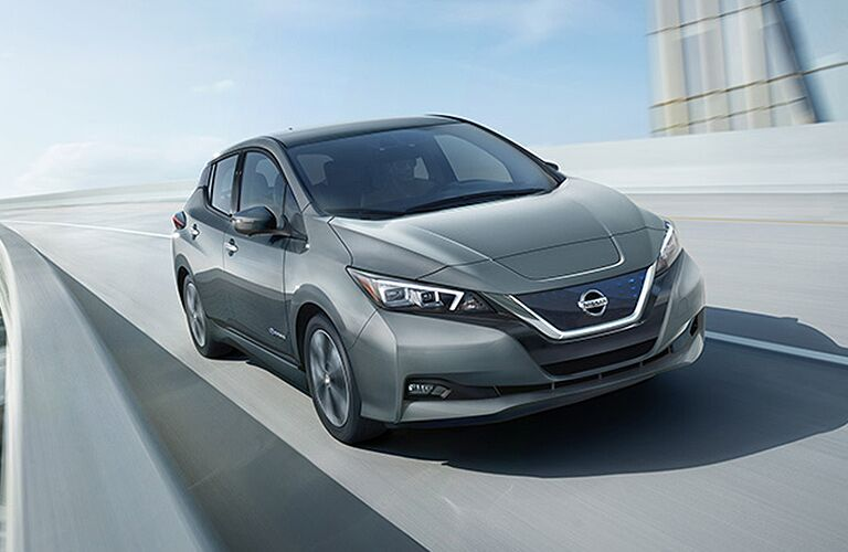 silver Nissan Leaf driving fast on a highway