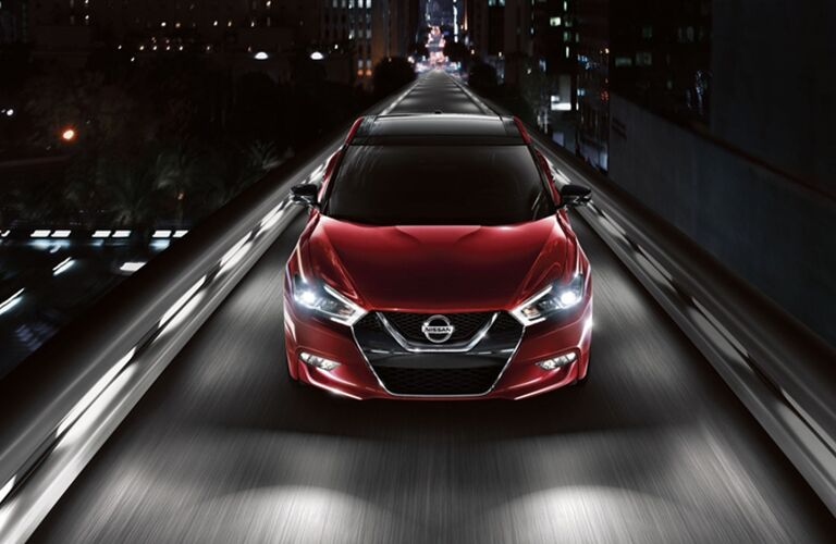 red Nissan Maxima leaving the city behind it on a one lane highway