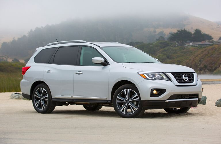 gray Nissan Pathfinder with trees and hills in the background