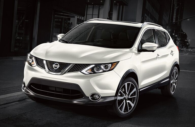 white Nissan Rogue Sport on a black and white city street