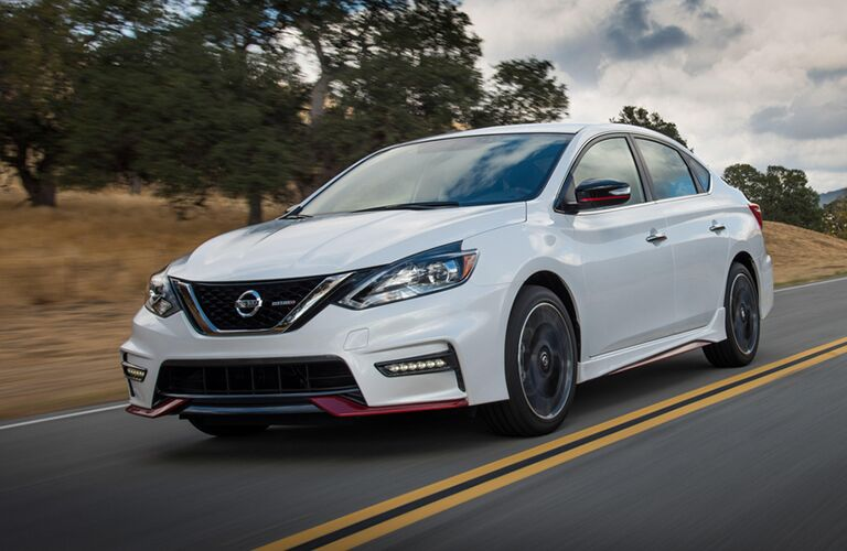 white Nissan Sentra with red exterior trim on country highway