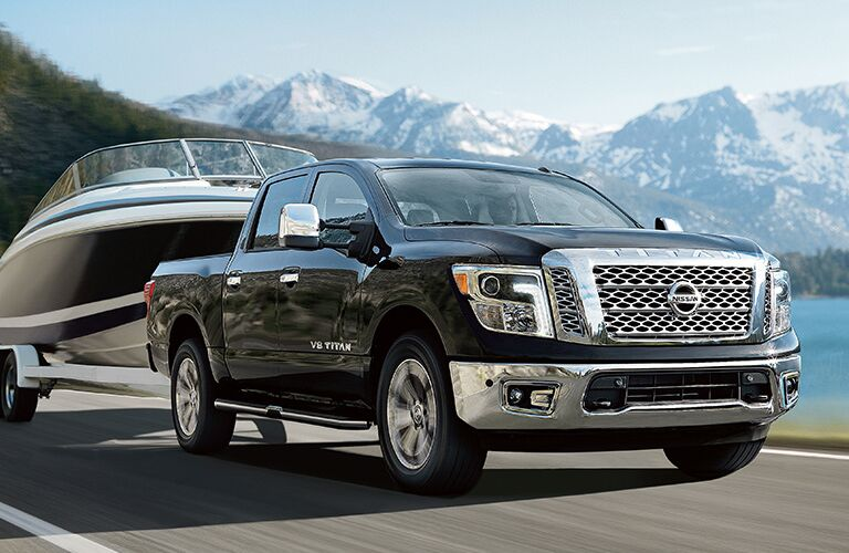 black Nissan Titan towing a boat with a lake and mountains in the background