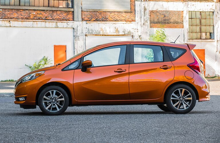 orange Nissan Versa Note stopped in the middle of the road in front of an old dilapidated building