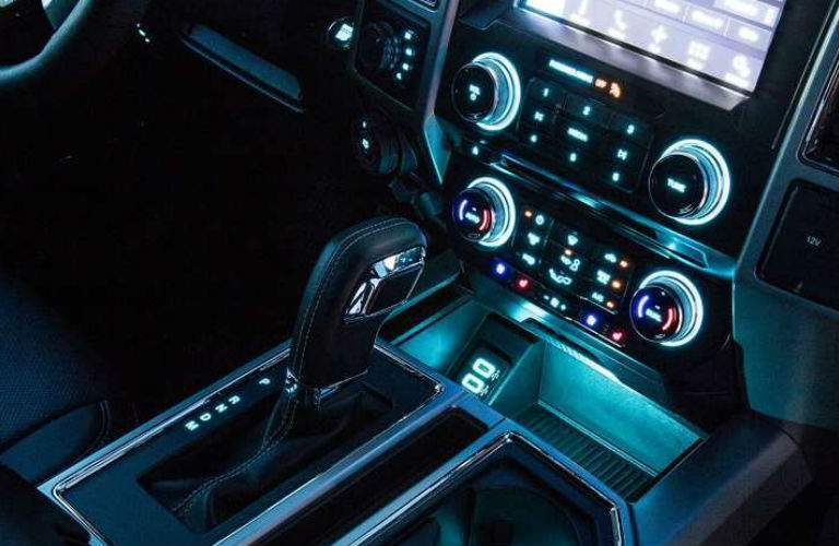 View of the infotainment knobs and gear shifter, all a-glow in futuristic blue lighting.