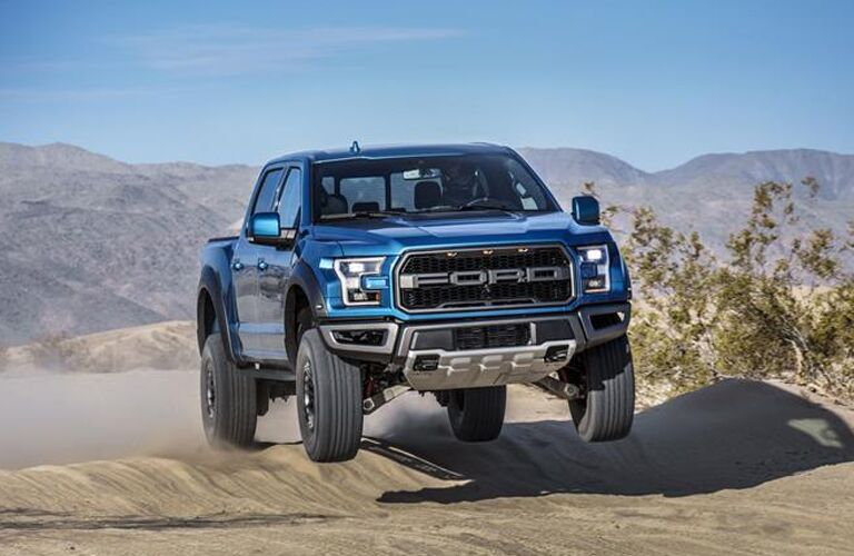 Blue 2019 Ford F-150 Raptor leaps over a mound of dirt in the desert on the off-roading adventure of a lifetime.