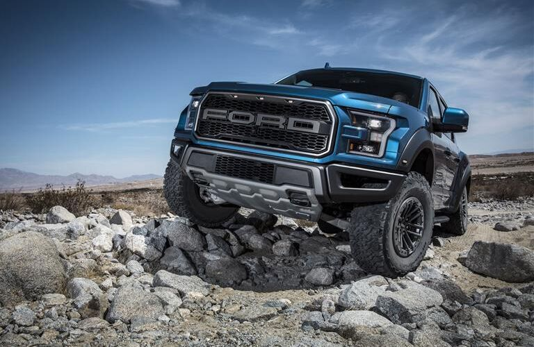 Blue 2019 Ford F-150 Raptor climbs over a pile of rocks in the off-road adventure of a lifetime.