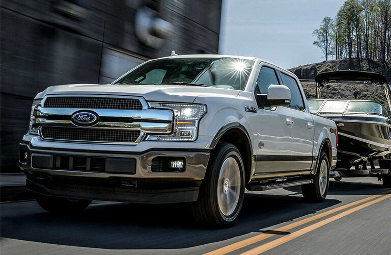 Front driver angle of a white 2019 Ford F-150 pulling a boat in the city