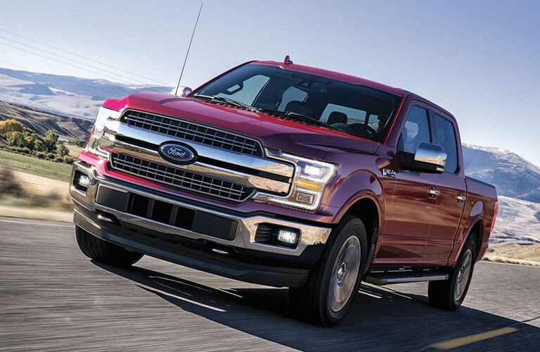 A red 2019 Ford F-150 drives down a desert highway.