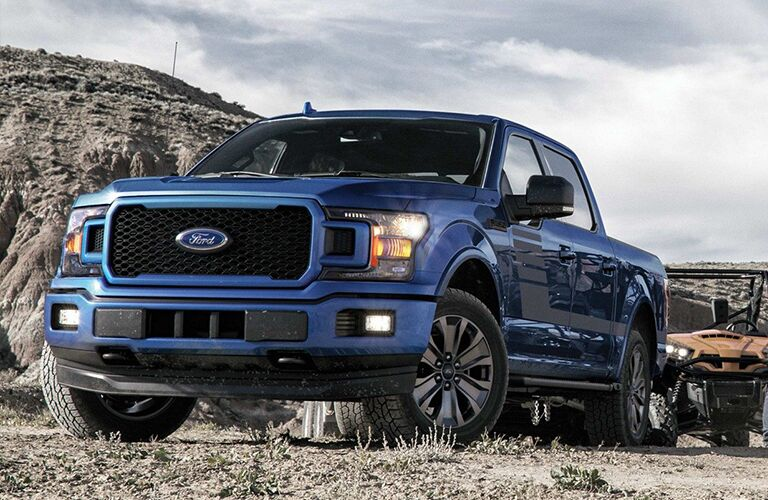 Blue 2019 Ford F-150 drives in a rugged dry landscape.