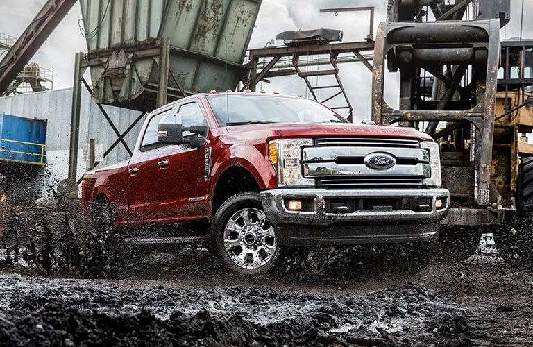 A red 2019 Ford F-250 sloshes through the mud on a construction site. Exterior angled front/side view.