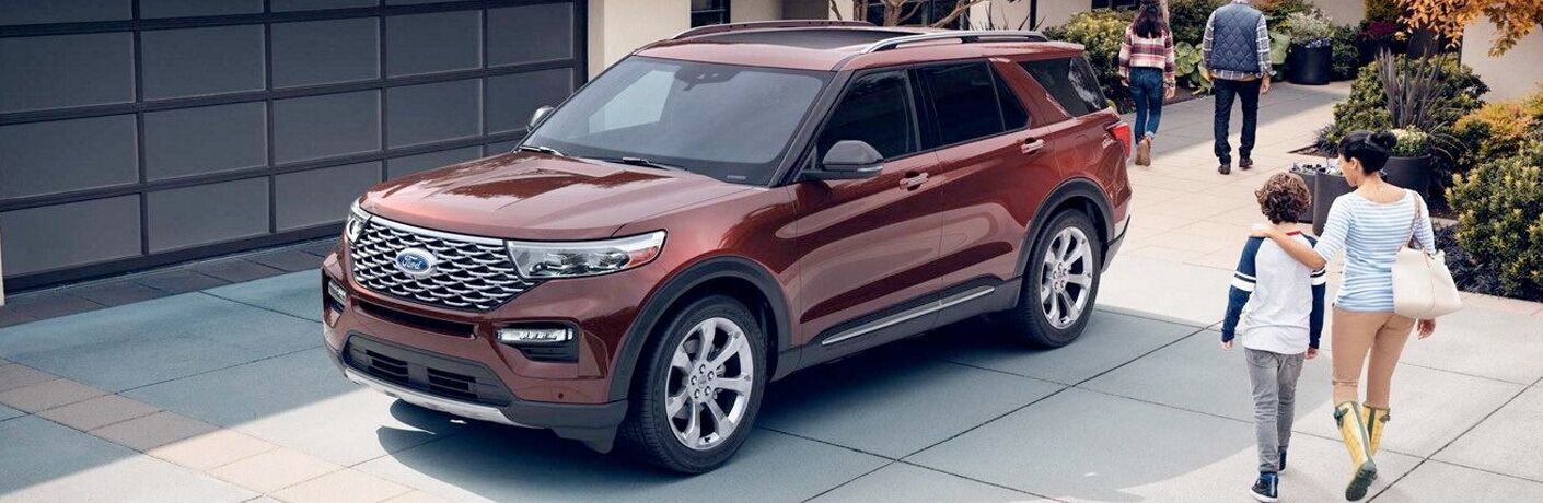 Red 2020 Ford Explorer parked in a driveway as a family strolls past.