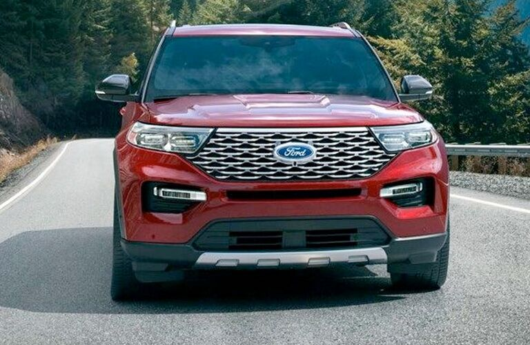 Head-on view of a red 2020 Ford Explorer driving down a forest-lined highway.