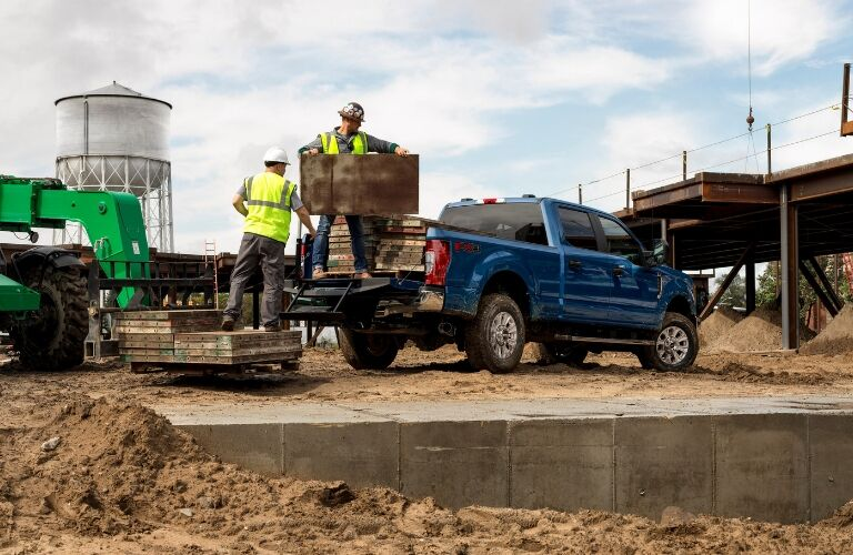 Two men on a construction site load a variety of heavy materials into the back of a blue 2020 Ford F-250 Super Duty truck.