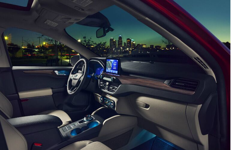 Interior front seat of the 2020 Ford Escape. Through the windows a city skyline is visible against the late-evening sky.