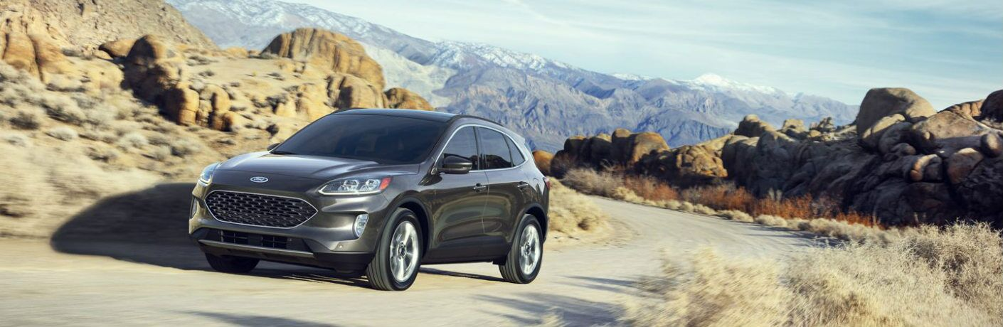 A dark colored 2020 Ford Escape drives up a mountain path in the midst of desert. Exterior front/side angled view.