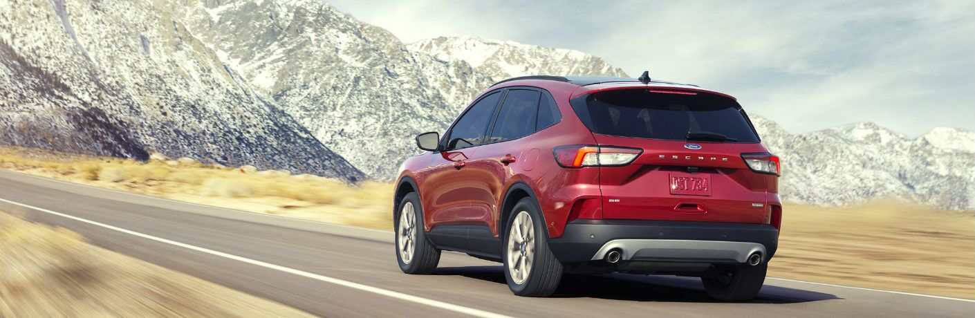 Red 2020 Ford Escape drives down a highway towards some towering snowy peaks. Exterior rear/side angled view.