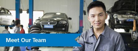 "Man in car shop looking at camera with car in background and ""Meet our Team"" text"