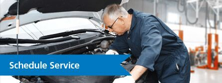 "Mechanic leaning over car with blue ""schedule service"" banner to the left"