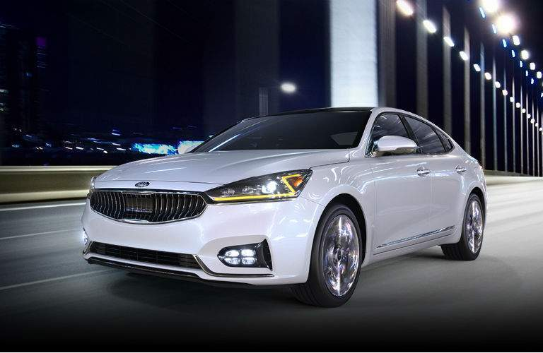 2018 kia cadenza in white driving at night on a bridge